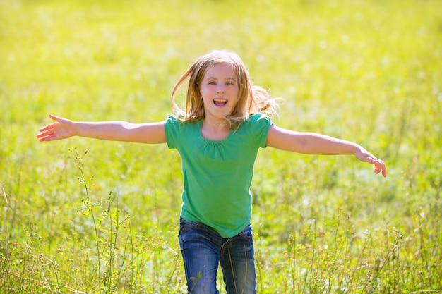 Niño niña feliz corriendo manos abiertas en verde al aire libre