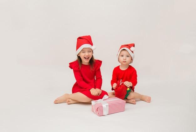 Niño y niña feliz en gorras rojas sobre blanco