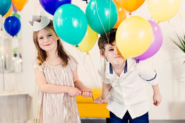 Niño y niña con globos sonriendo