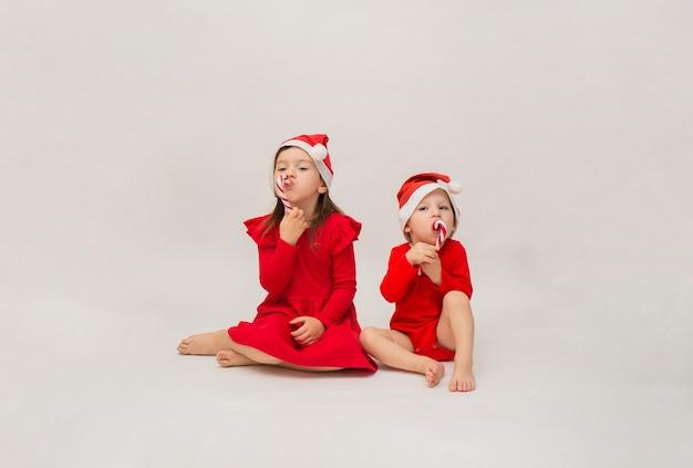 Niño y niña con gorras rojas se sientan con piruletas en blanco