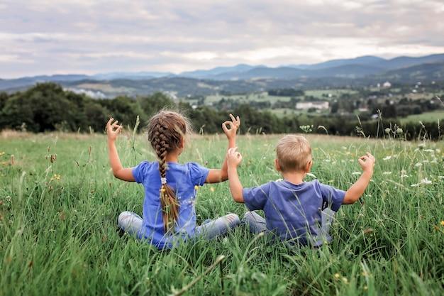 Niño y niña haciendo los ejercicios matinales en la cima de las montañas