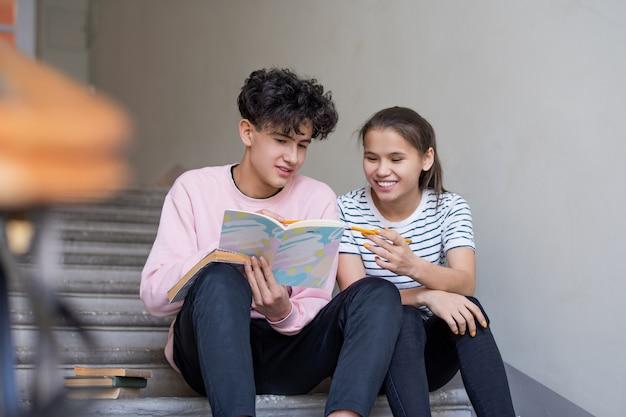 Niño y niña inteligente apuntando a la página del cuaderno mientras se discuten las notas de la conferencia en la escalera antes del seminario en el descanso
