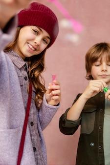 Niño y niña jugando con pompas de jabón