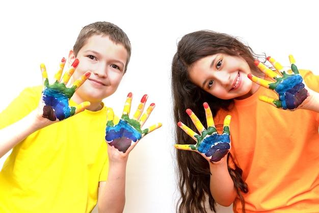 Un niño y una niña miran a la cámara y muestran sus palmas en pinturas. arco iris en las manos. día mundial del niño.