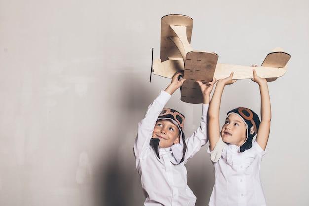 Niño y niña con modelo de avión de madera y una gorra con gorra