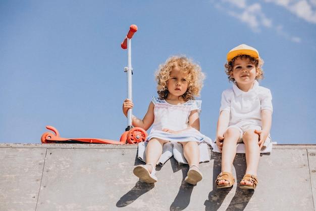Niño y una niña montando scooter juntos en el parque