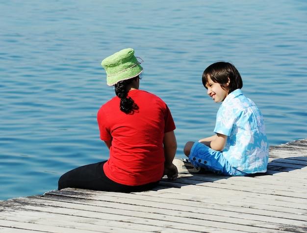 Niño y niña en el muelle de madera en un hermoso mar