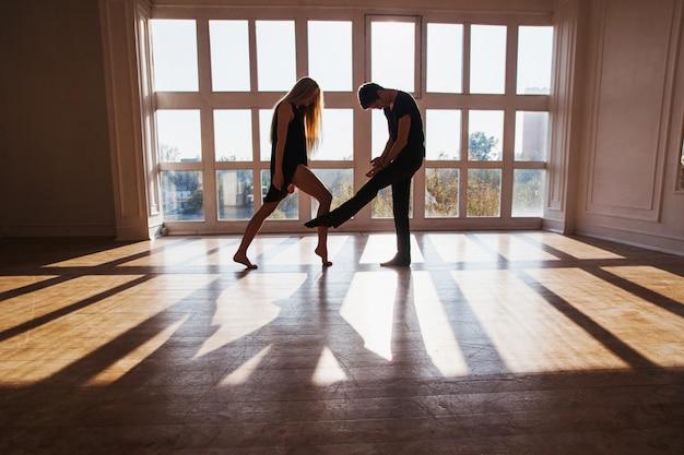 Un niño y una niña con el pelo largo y rubio de pie delante de la ventana. bailarines durante un entrenamiento. problemas y dificultades en las relaciones. la difícil situación en la vida. fotografía conceptual