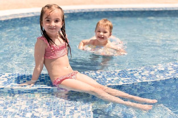 Niño y niña en la piscina
