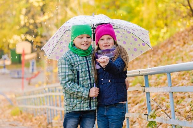 Niño y niña preadolescente caminando en el parque lloviendo