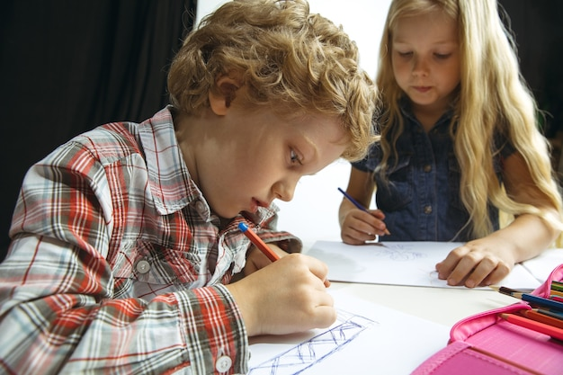 Niño y niña preparándose para la escuela después de un largo receso de verano. de vuelta a la escuela. pequeños modelos caucásicos dibujando juntos sobre fondo blanco y negro. concepto de infancia, educación, vacaciones o deberes.