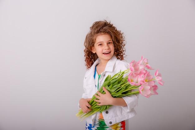 Un niño, una niña con un ramo de tulipanes amarillos