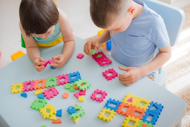 Un niño y una niña recogen un suave rompecabezas en la mesa.