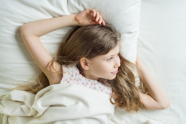 Niño niña rubia con el pelo largo y ondulado se despierta.