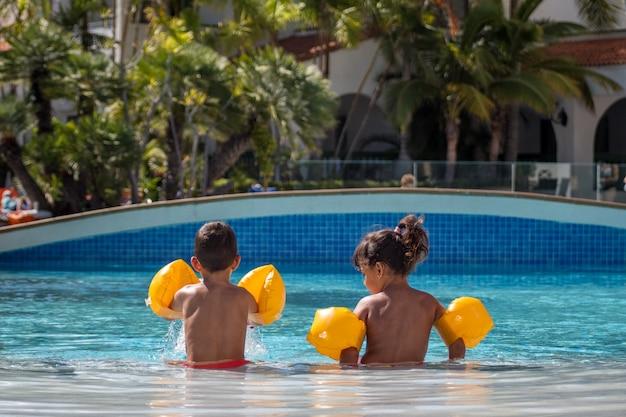 Niño y niña sentados uno al lado del otro en el borde de la piscina. vacaciones de verano con niños