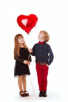 Niño y niña sobre un fondo blanco con un globo rojo corazón