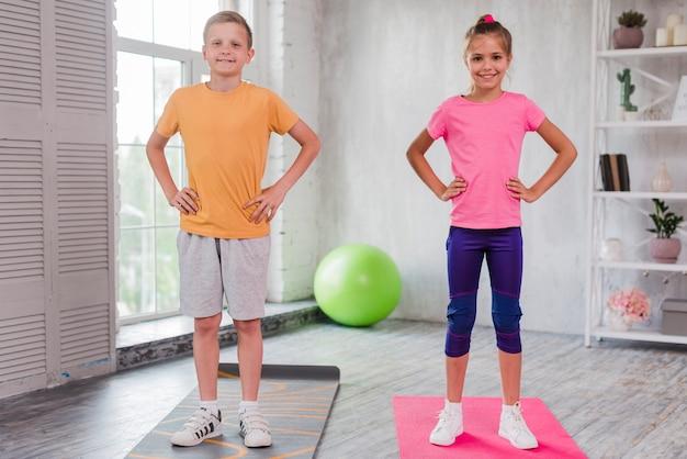 Niño y niña sonrientes que se colocan en la estera del ejercicio con las manos en cadera