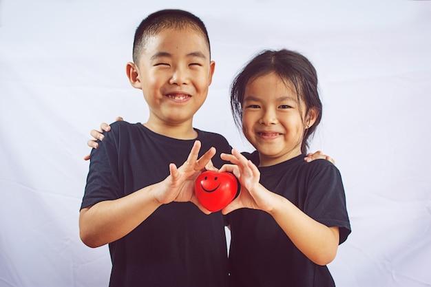 Niño y niña tienen corazón rojo