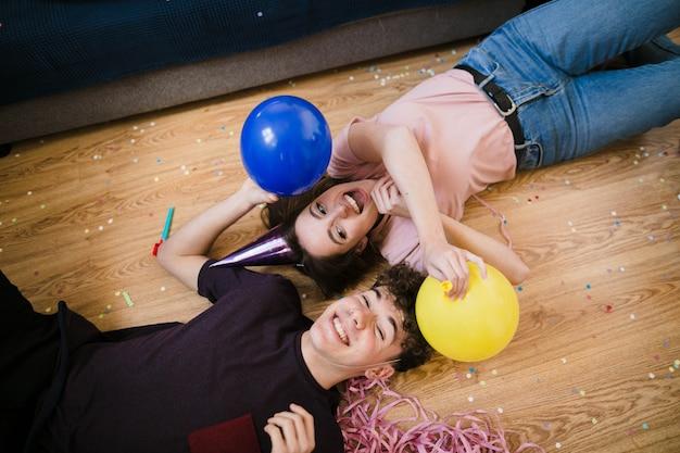 Niño y niña tirado en el piso con globos