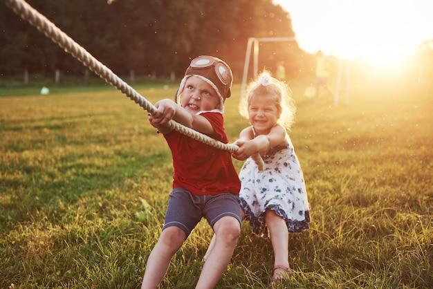 Niño y niña tirando de una cuerda y jugando tira y afloja en el parque