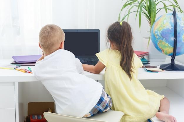 Niño y niña usando una computadora portátil en la escuela.