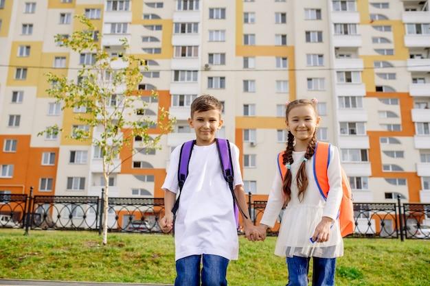Niño y niña van a la escuela de la mano en el fondo de la fachada del nuevo edificio