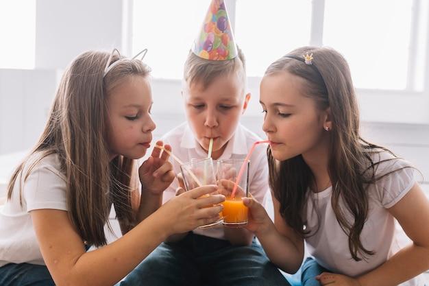 Niño y niñas bebiendo en la fiesta de cumpleaños
