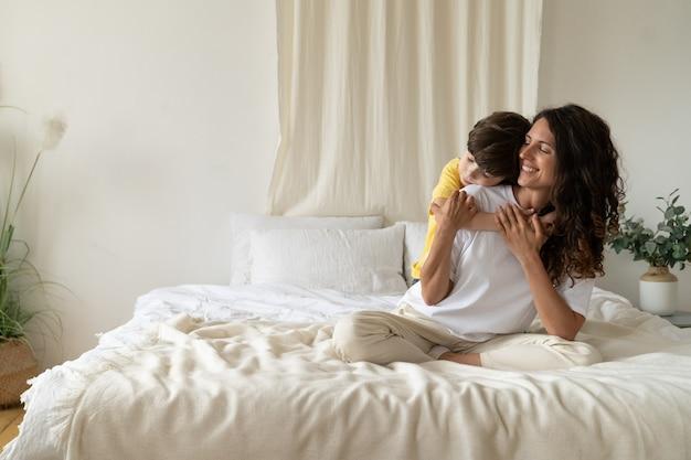 Niño, niño, abrazar, sonriente, mamá, en, mañana, sentarse, en, cama, llevando, pijama, en casa, el, fin de semana, amor familiar