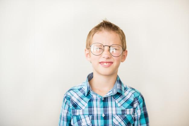 Niño niño adolescente entrecierra los ojos con gafas de corrección de miopía