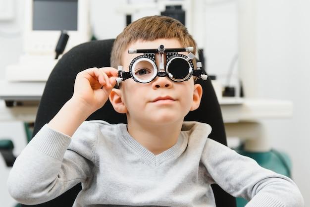 Niño niño alegre en gafas comprueba la visión del ojo oftalmólogo pediátrico.