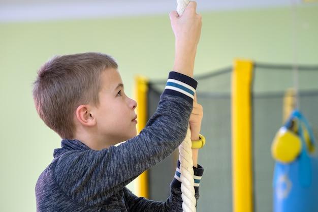 Niño niño ejercicio en una barra de escalera de pared dentro de la sala de gimnasio deportivo en una escuela.