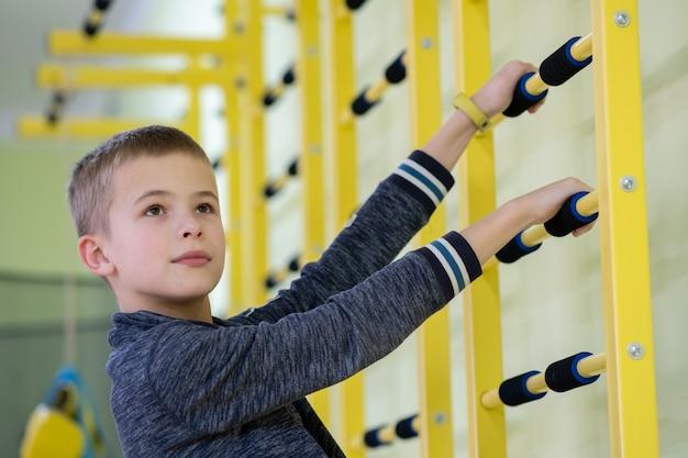 Niño niño haciendo ejercicio en una barra de escalera de pared dentro de la sala de gimnasia deportiva en una escuela.