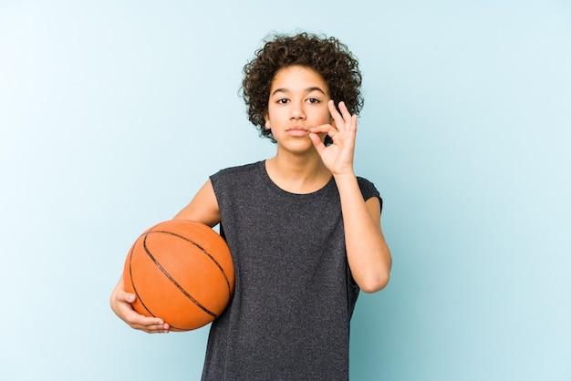 Niño niño jugando baloncesto aislado sobre fondo azul con los dedos en los labios guardando un secreto.