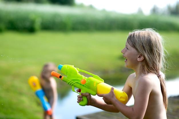 Niño niño, niña jugando con juguete de pistola de agua en el verano.