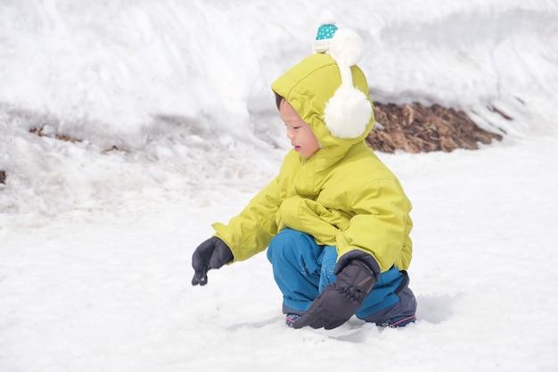 Niño niño niño con orejeras, guantes de nieve jugando alegremente en la nieve