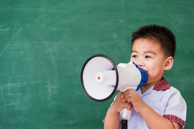 Niño niño preescolar en uniforme de estudiante hablando a través del megáfono contra