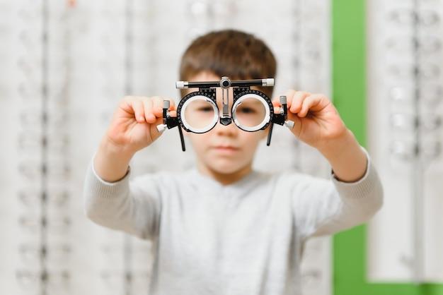 Niño niño que muestra el marco de prueba en la clínica de oftalmología, enfoque selectivo
