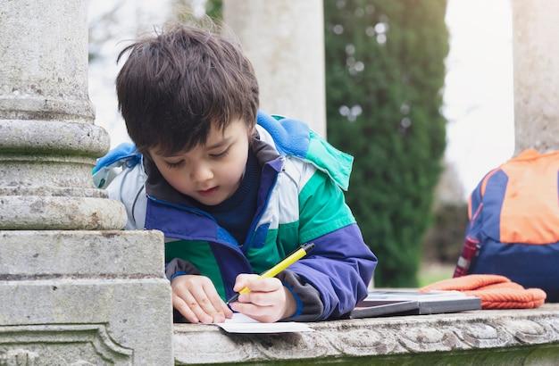 Niño niño que sostiene una pluma y escribe o dibuja en un papel sobre lo que encuentra en el camino al bosque