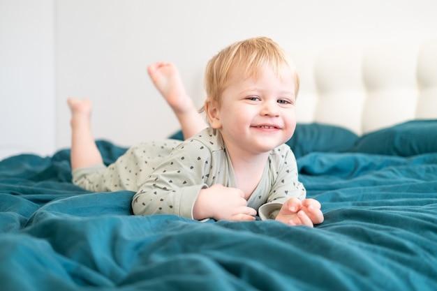 Niño niño sano en pijama verde divirtiéndose acostado en la cama en casa.