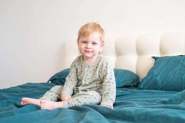 Niño niño sano en pijama verde sonriendo sentado en la cama en casa.