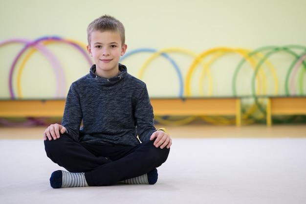 Niño niño sentado en el suelo dentro de la sala de deportes