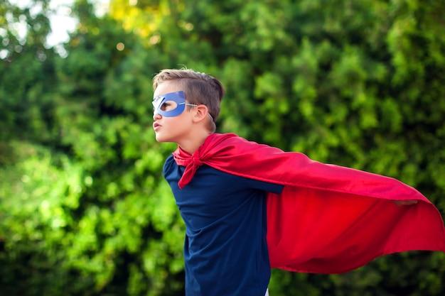 Niño niño superhéroe contra verde al aire libre
