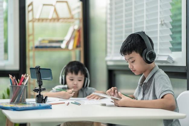 El niño niño está utilizando se comunica en internet en casa.