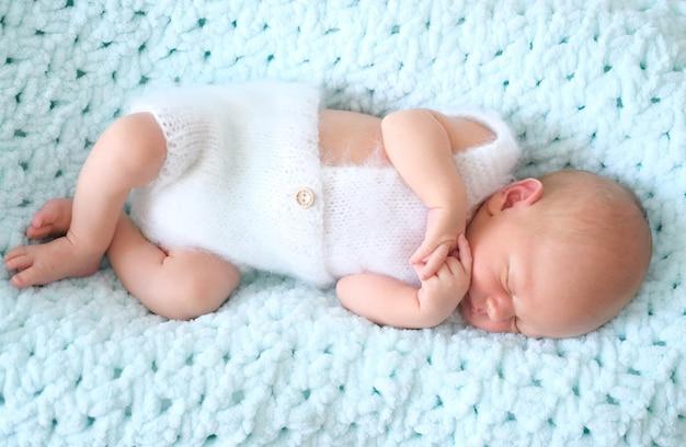 Niño o niña recién nacido durmiendo se encuentra en una manta de lana azul