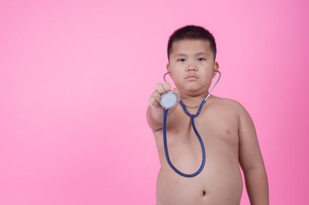 Niño obeso que tiene sobrepeso sobre un fondo rosa.
