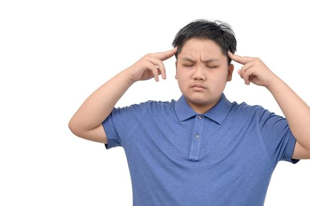 Niño obeso siente tensión o dolor de cabeza aislado sobre fondo blanco, concepto de atención médica