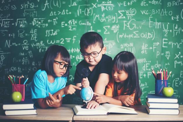 Niño observando o estudiando el modelo de globo educativo en el aula.