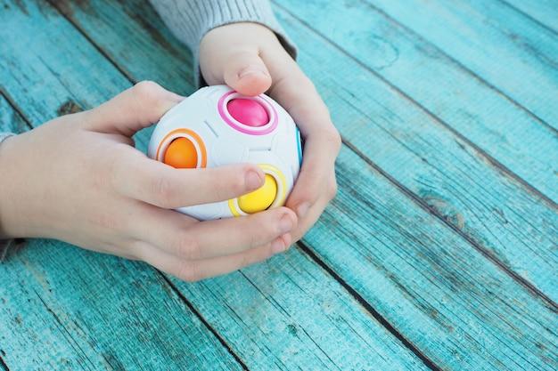 El niño está ocupado con un rompecabezas en forma de una bola con bolas de colores dentro sobre un fondo de madera azul.