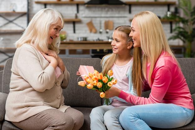 El niño ofrece un ramo de flores a su abuela.