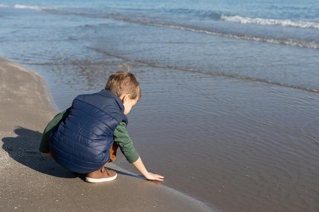 Niño en la orilla de la playa jugando con las olas.